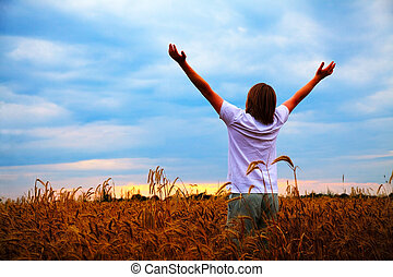 Young man staying with raised hands at sunset time - Young...