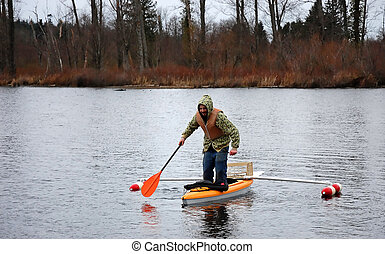 Man Standing in Canoe - This young man is standing in a...