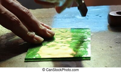 glass cutting - close up hands cutting green glass for...