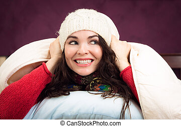 Happy woman peeking out from under blankets - A beautiful...