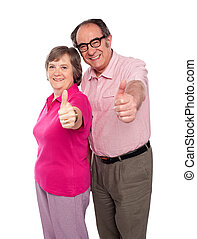 Senior couple gesturing thumbs up