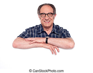 Smiling aged man posing with blank billboard