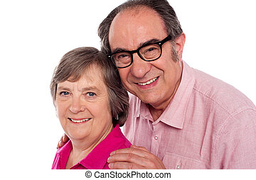 Closeup portrait of smiling aged couple looking at camera
