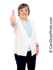 Smiling old lady showing thumbs up gesture to camera....