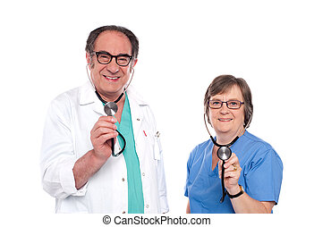 Smiling aged male and female doctors posing with stethoscope