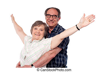 Mature woman with arms outstretched while man hugging her...