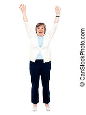 Excited senior woman posing with raised arms Enjoying...