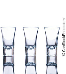 Three empty shot glasses on a reflective surface. Isolated...