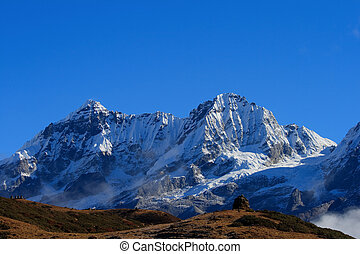The high snow-capped mountains against the blue sky