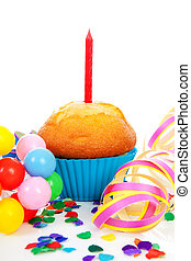 Birthday cupcake with candle, party streamers and colorful confetti over white background