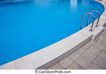 Swimming pool with blue water and a ladder