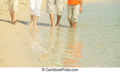 Calm water - Barefoot people strolling through calm clear...