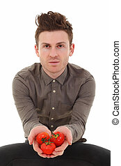 Young man offering tomatoes
