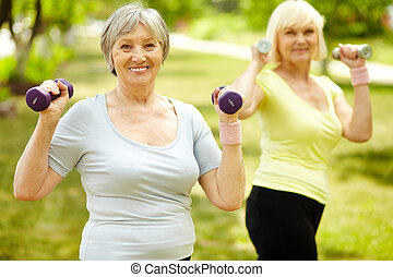 Exercise for biceps - Portrait of aged women doing physical...