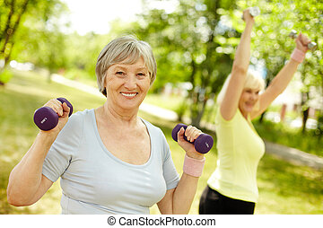 Summer workout - Pleasant mature females working out in the...