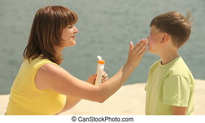 Caring mother - Smiling mom applying sunscreen cream on the...