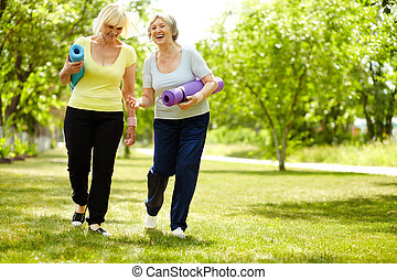 Happy time - Portrait of two happy senior females walking...