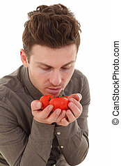 Young man smelling organic tomatoes