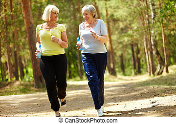 Recreation - Portrait of two senior females running outdoors