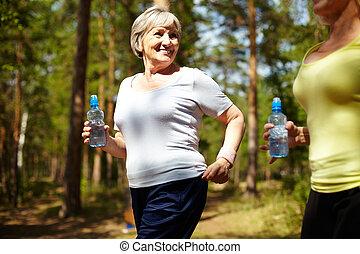Runner - Senior female with bottle of water running outdoors