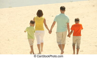 Holding hands - Family of four strolling across the beach...
