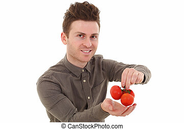 Young man smiling with tomatoes