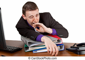Tiredness - Young businessman yawning at his desktop -...