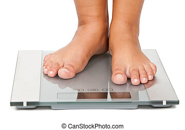Weight - Young woman standing on bathroom scales