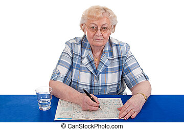 Crossword puzzle - Elderly woman solving a crossword puzzle...