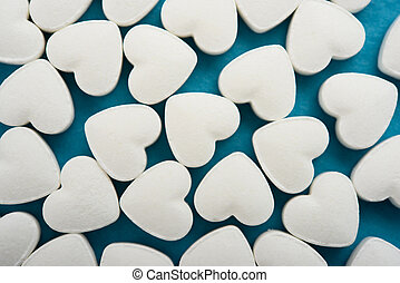 Pills as a heart on blue background