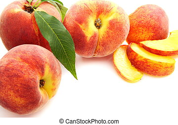 Fruits of peach with green leaves.