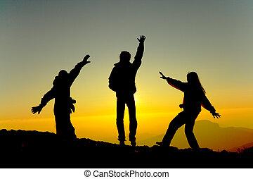 Happy men silhouette  at sunrise