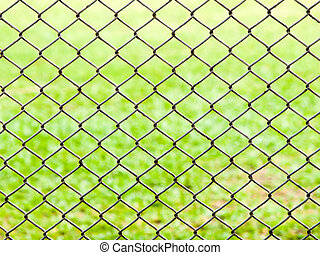 iron wire fence on green grass background .