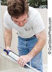 Handyman Caulking - Handyman using a caulking gun to caulk a...