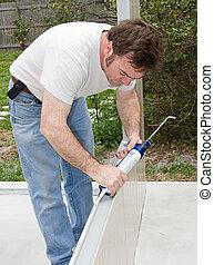 Caulking Project - Handyman using a caulking gun to caulk a...
