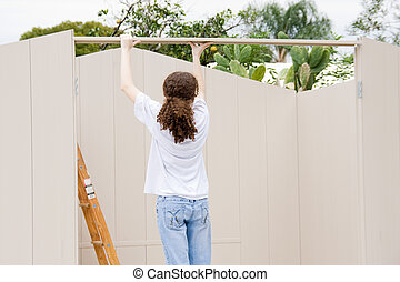 Teen Builds Shed - Teen girl working on building a shed