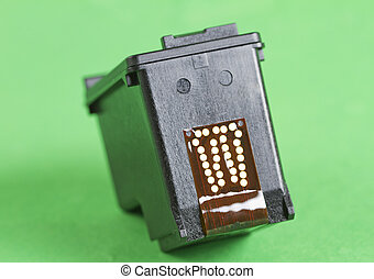 Cartridge - Black cartridge for a printer over a green...