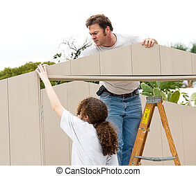 Working Together - Father and daughter working on a home...