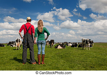 Typical Dutch landscape with farmer couple and cows -...