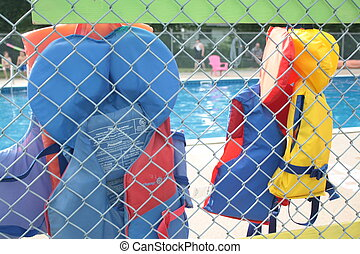 lifejackets by pool - lifejackets hanging by a fence at a...