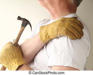 home maintenance with shoulder pain - a man grasps his...