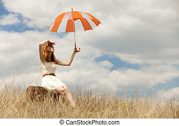 Beautiful redhead girl with umbrella and suitcase at outdoor...