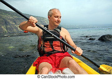 Man kayaking - Mature man kayaking in the ocean on Big...