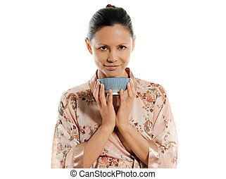 Portrait of beautiful Asian woman drinking tea in studio...