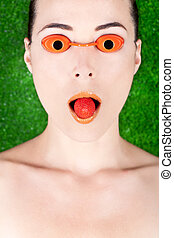 Woman wearing tanning bed glasses with strawberry in mouth -...