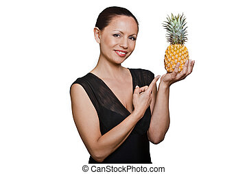 Portrait of beautiful Asian woman pointing at pineapple in...