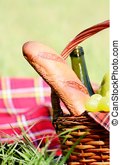 Picnic basket with red napkin fool of fruits, bread and wine...