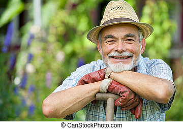 Senior gardener with a spade in the garden
