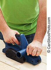 Male worker hands with electric planer
