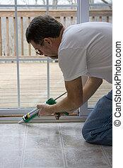 caulking doors - Contractor caulking around glass door...